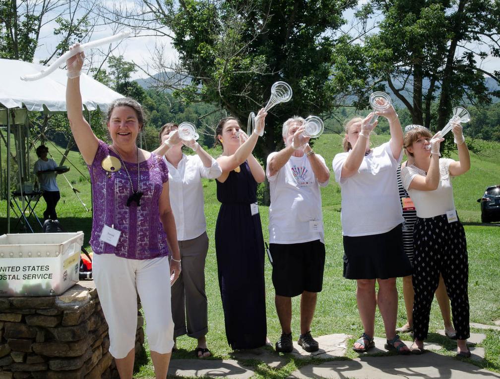 volunteers blowing Sally Prasch's glass horns