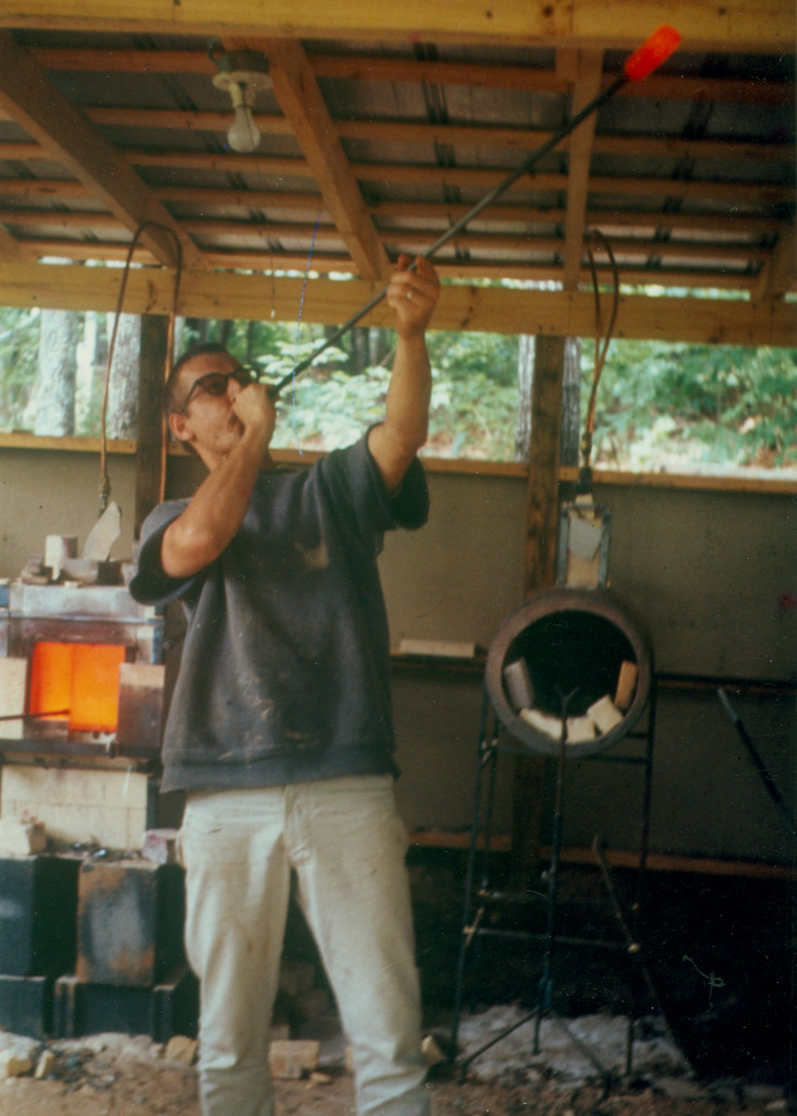 man blowing glass