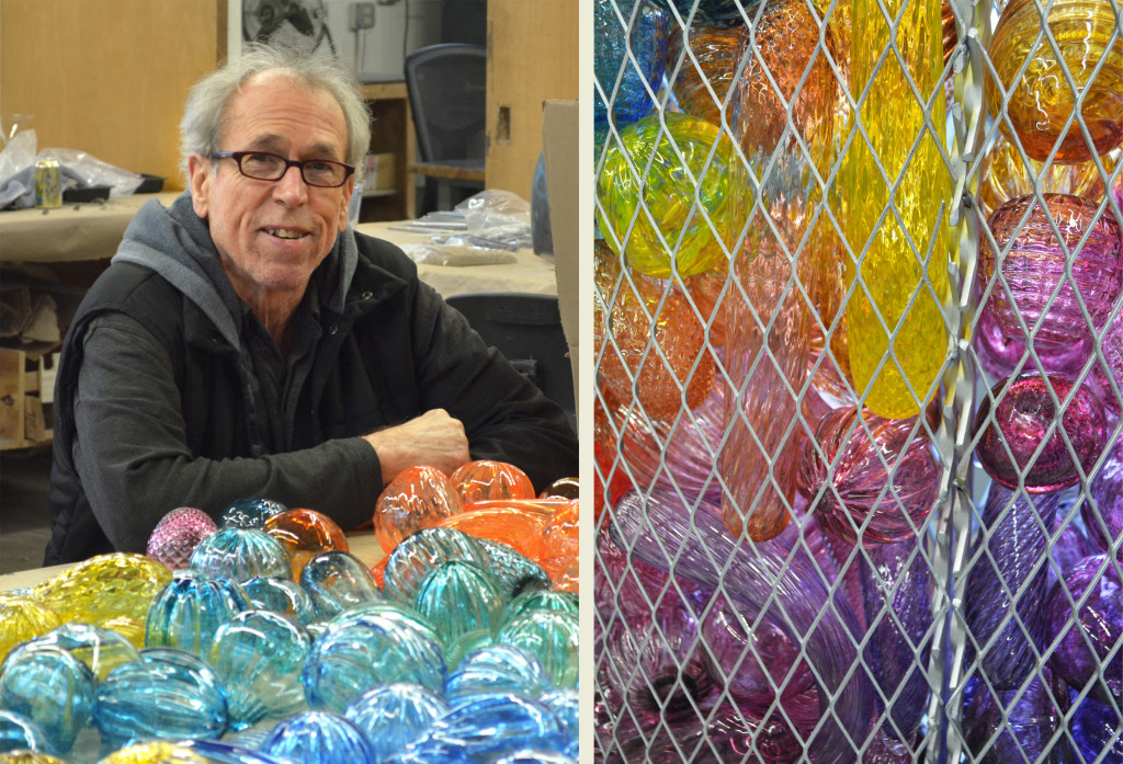 Jack Mackie posing with a handful of the week's glass orbs. At right is a close-up of the glass pieces layered inside one of the metal baskets that will adorn the installation.
