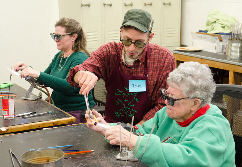 Each bead is formed by melting colored glass onto a metal rod.