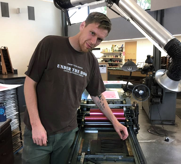portrait of Aaron Hughes working at the press in the letterpress studio