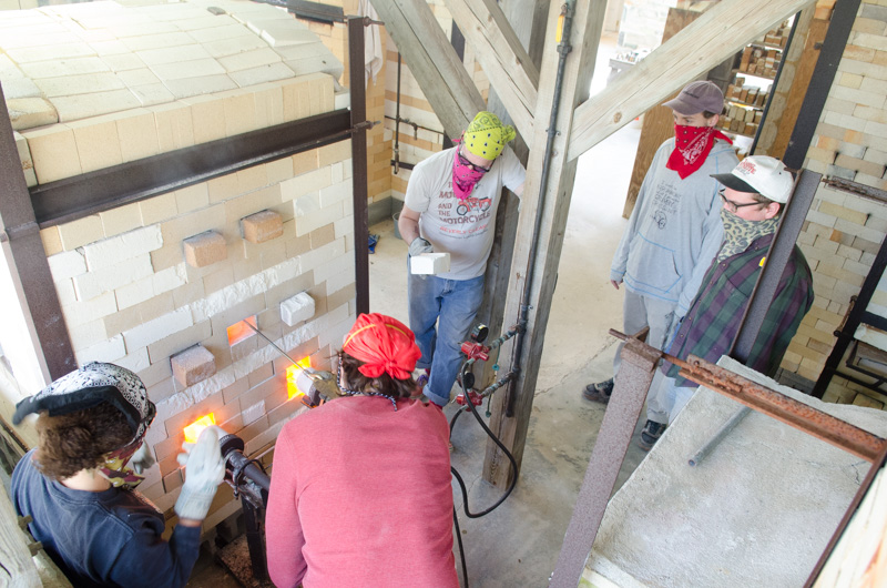 Students adding soda to a kiln during firing