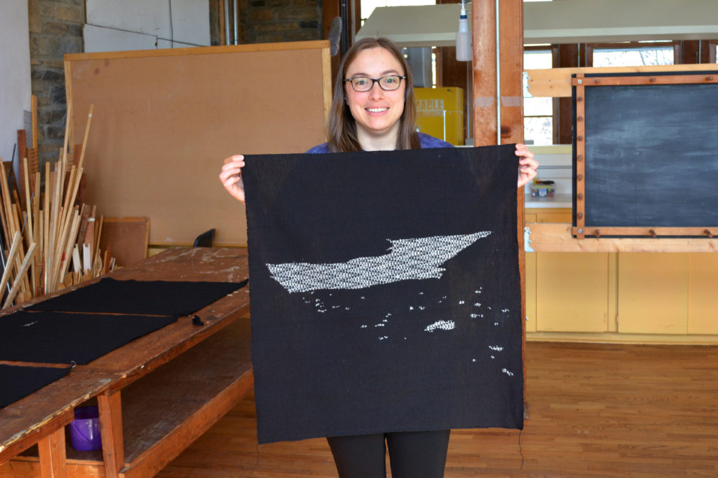 woman holding a panel woven in black and white