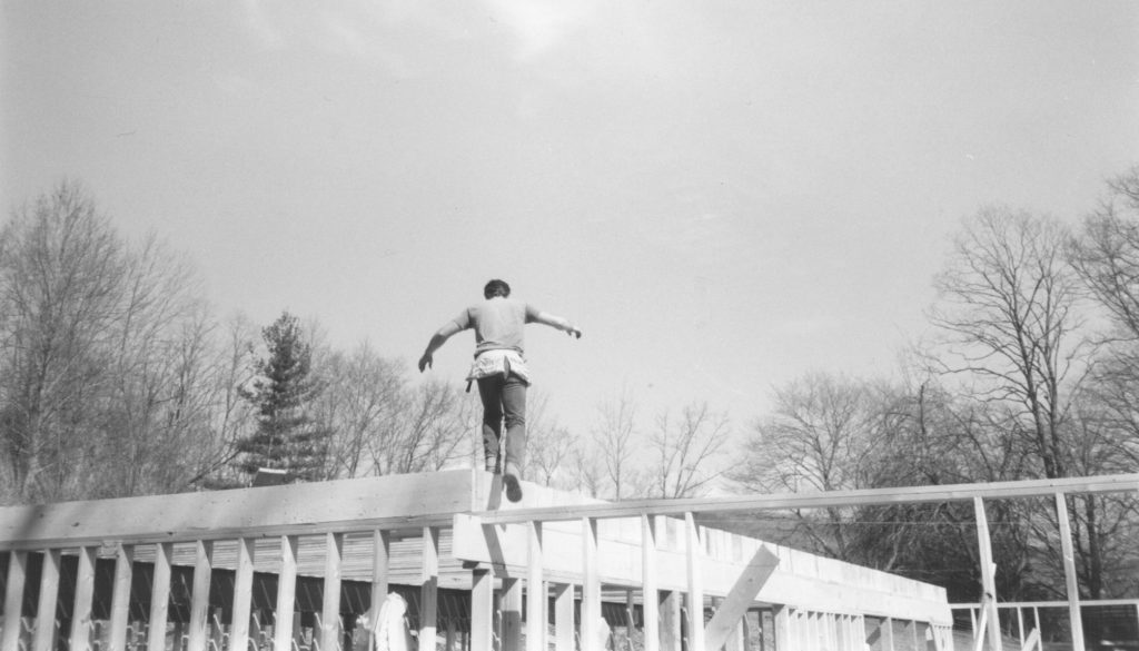 man balancing on a building under construction