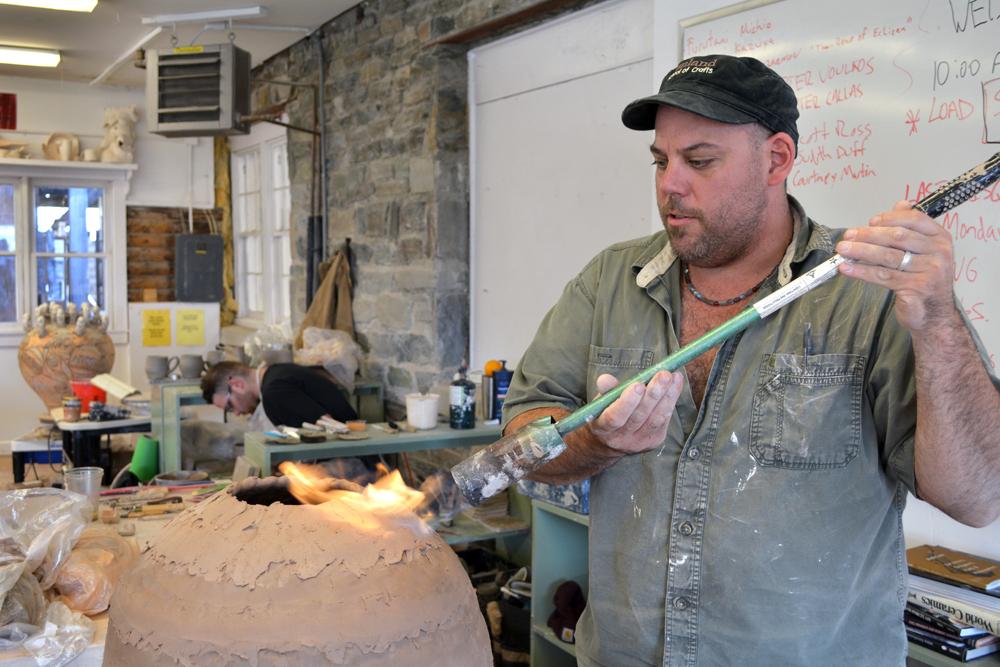 Nick Schwartz torching the top of a coil-built pot