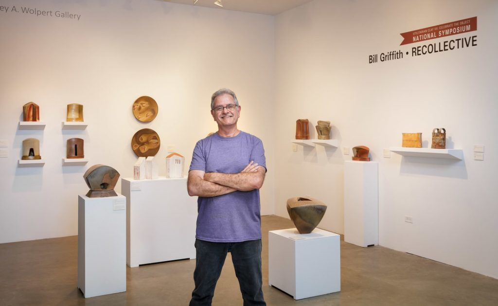 Bill Griffith stands with a display of his pots