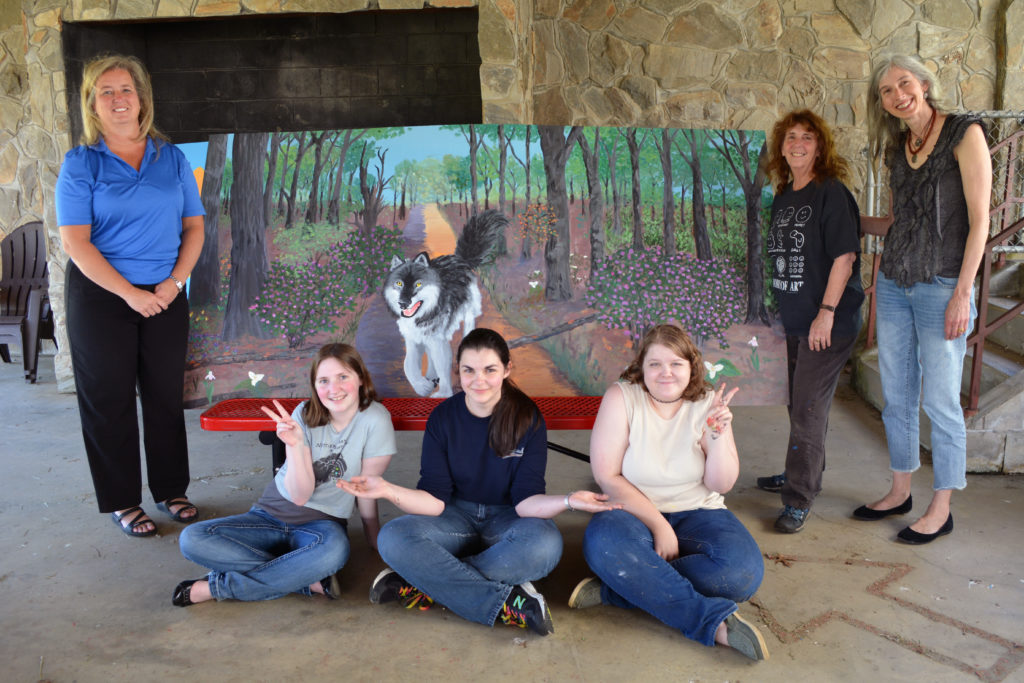 Students and others involved with the project pose with the completed wolf mural