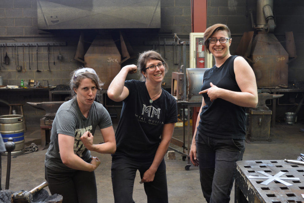 three women pose for a silly picture in the iron studio
