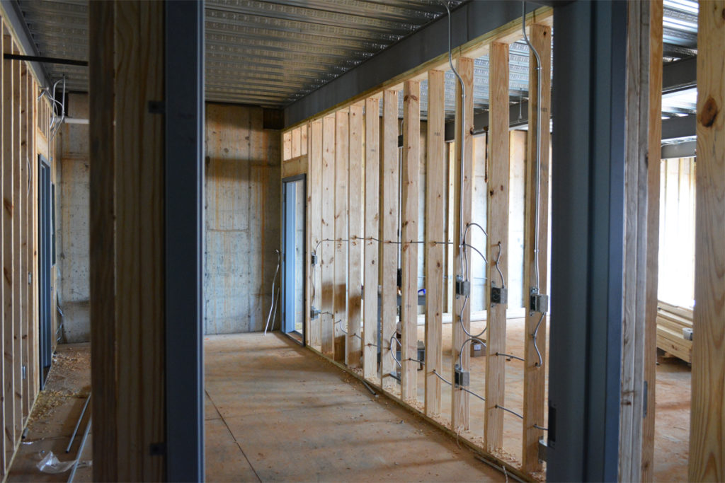 Framing out bathrooms and storage spaces behind the paper studio.