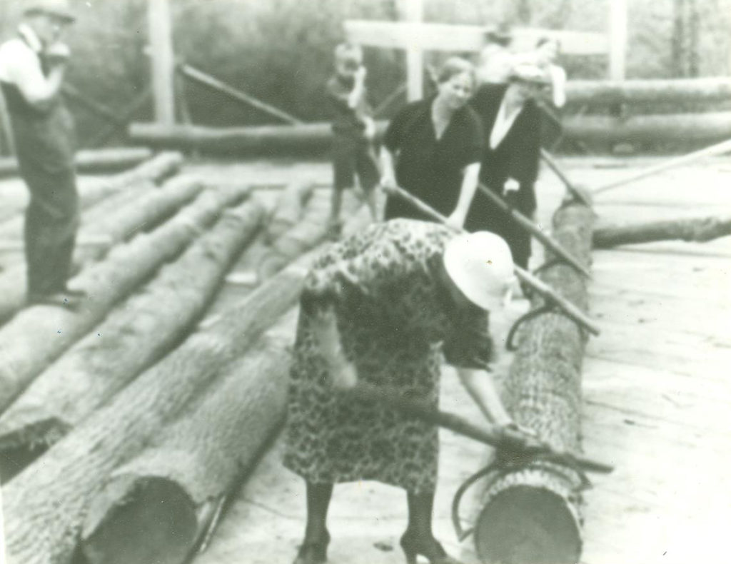 Using cant hooks to maneuver one of the building's sizable logs. The woman in the foreground is Lucy Morgan's sister Anna Barr.