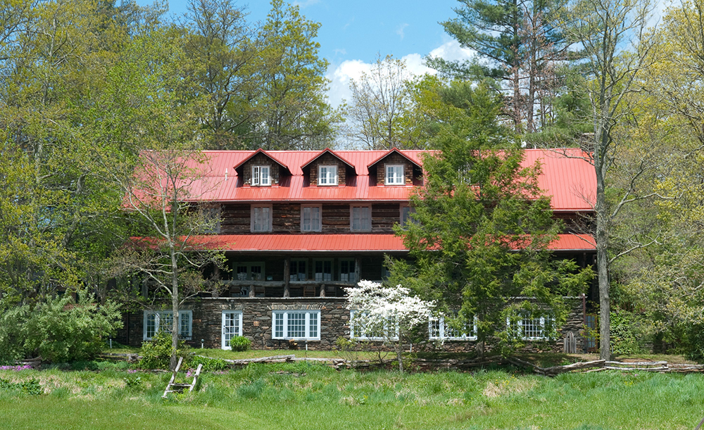 Front view of the Craft House with its iconic log porch and red roof