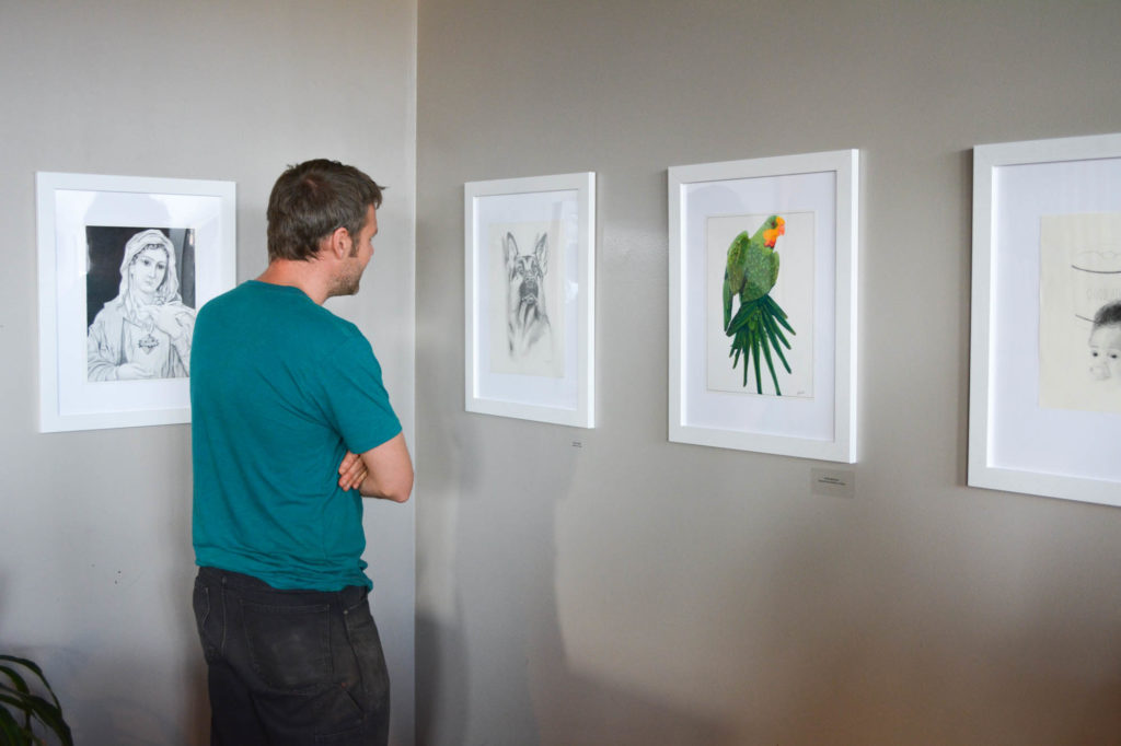 A viewer admiring some of the work, including portraits of a German shepherd and a parrot
