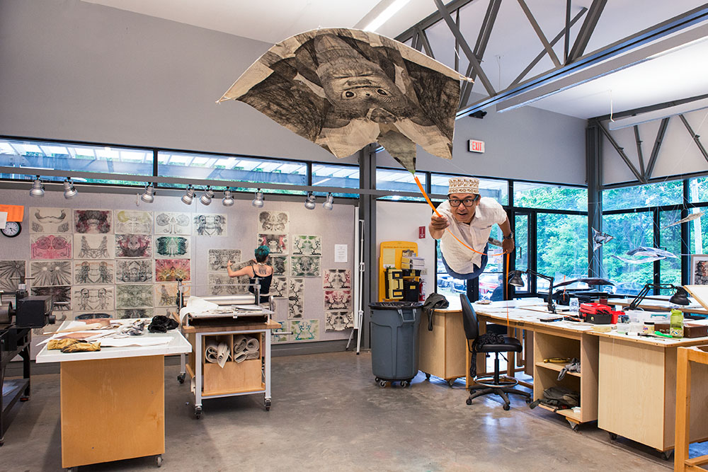 "Instructor Koichi Yamamoto ""flying"" with one of his kites in the printmaking studio"