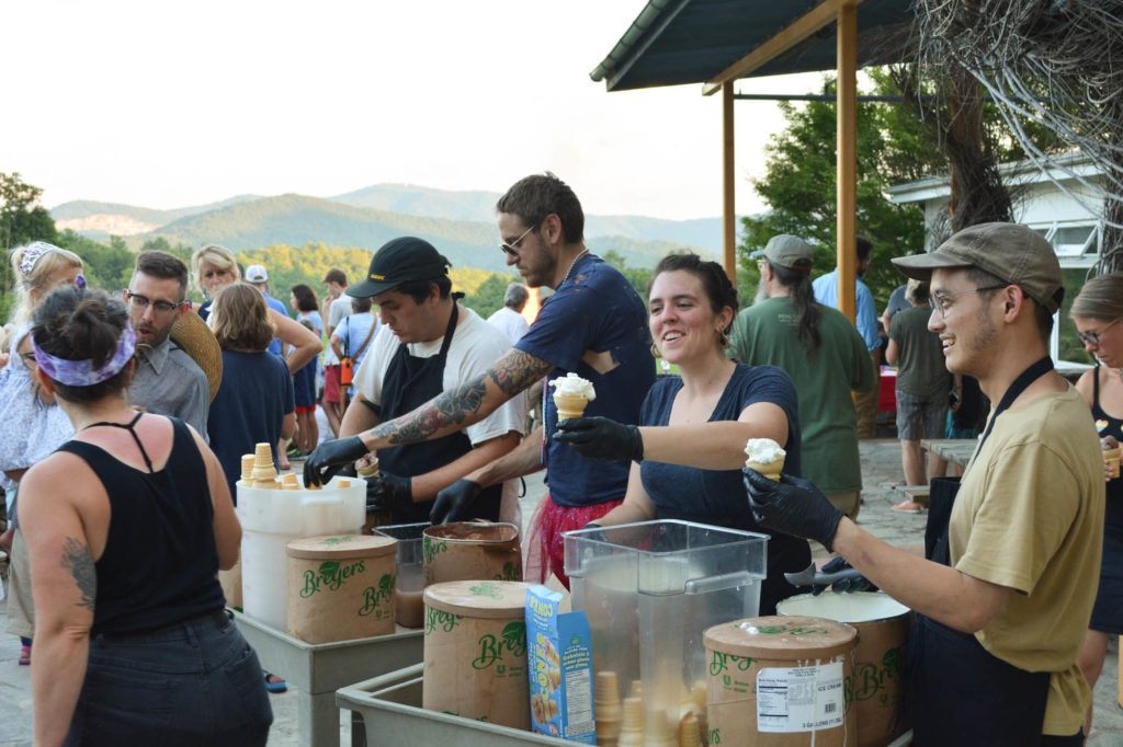 core fellows serve up ice cream from big cardboard tubs