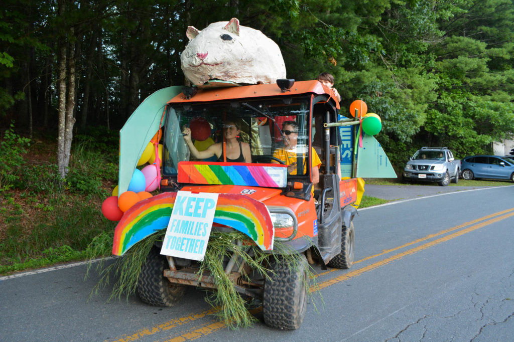 parade float with rainbows and a giant rat