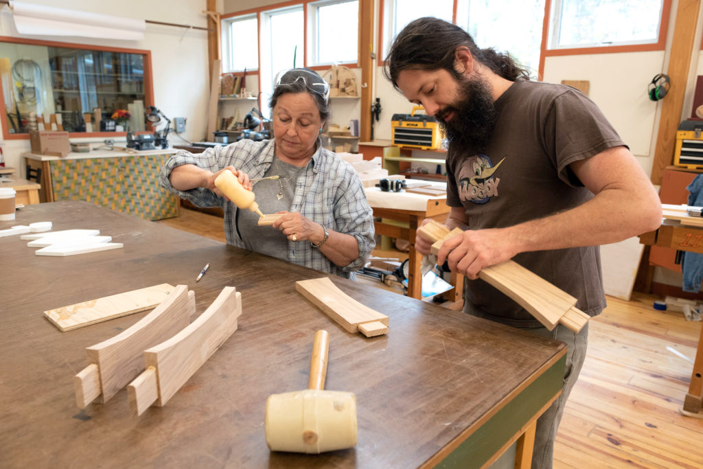 working together to glue up tenon joints in the wood studio