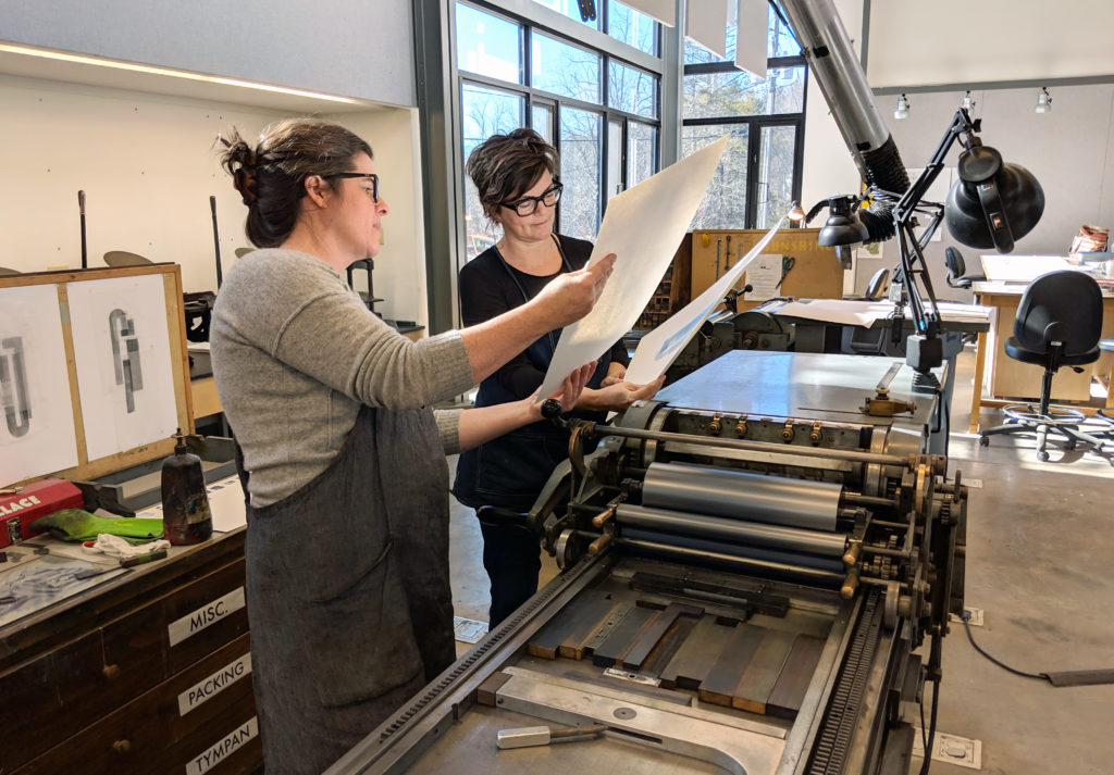 two women examining prints that have just come off a Vandercook press
