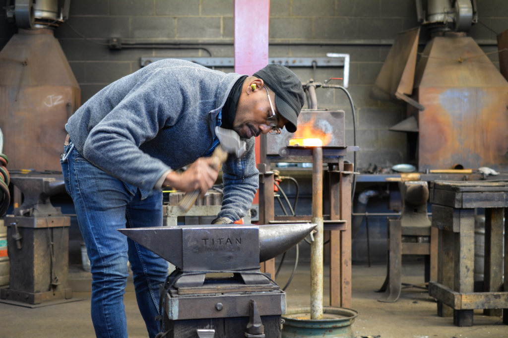 Metalsmith David Clemons working at the forge in the Penland iron studio