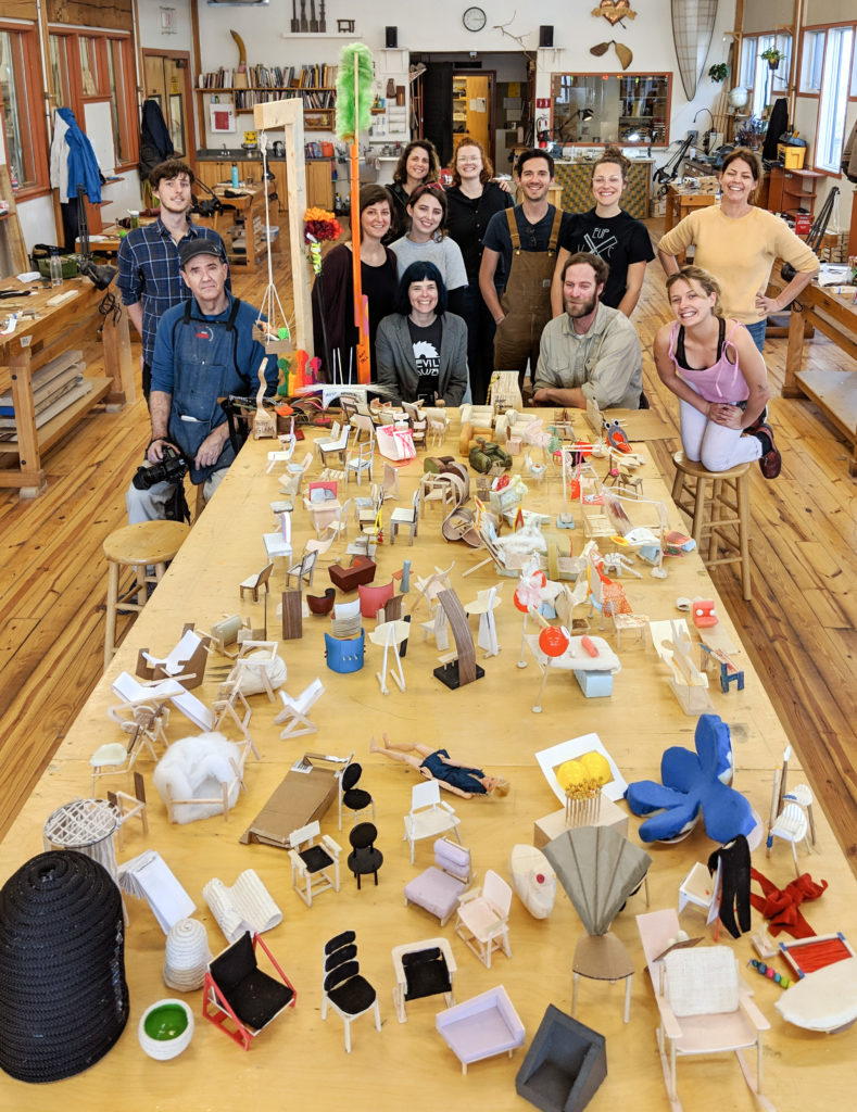 spring wood concentration students posing with a table full of mini chair models