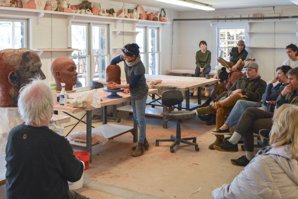 Cristina Cordova sculpting a head from red paper clay while a ring of students looks on