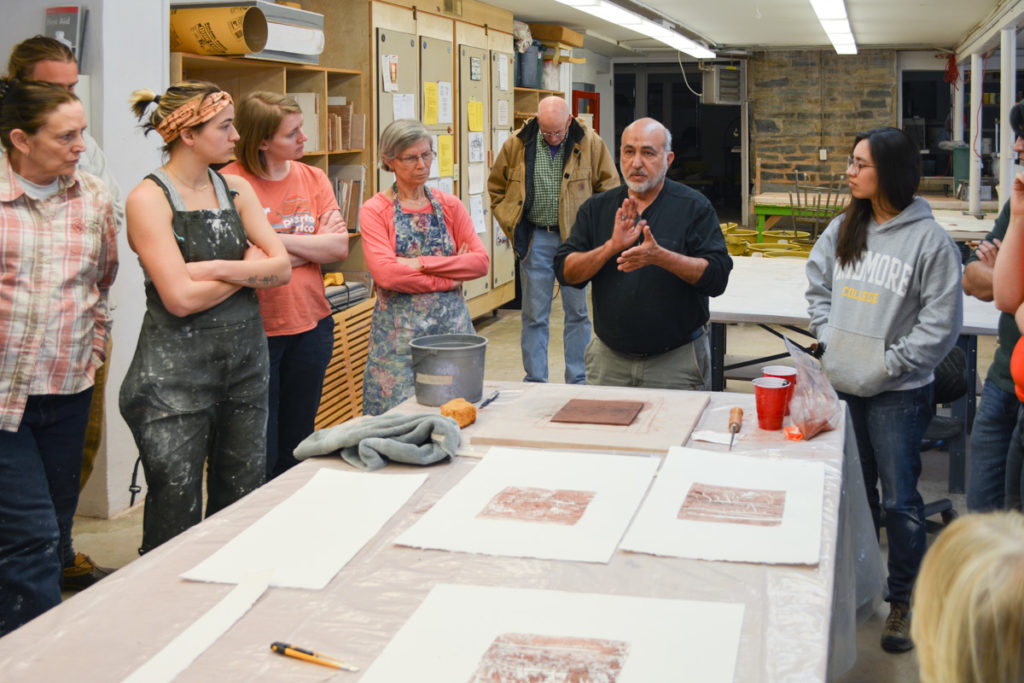 Artist Jaime Suarez giving a demonstration to a group of students on how to monoprint with clay and water