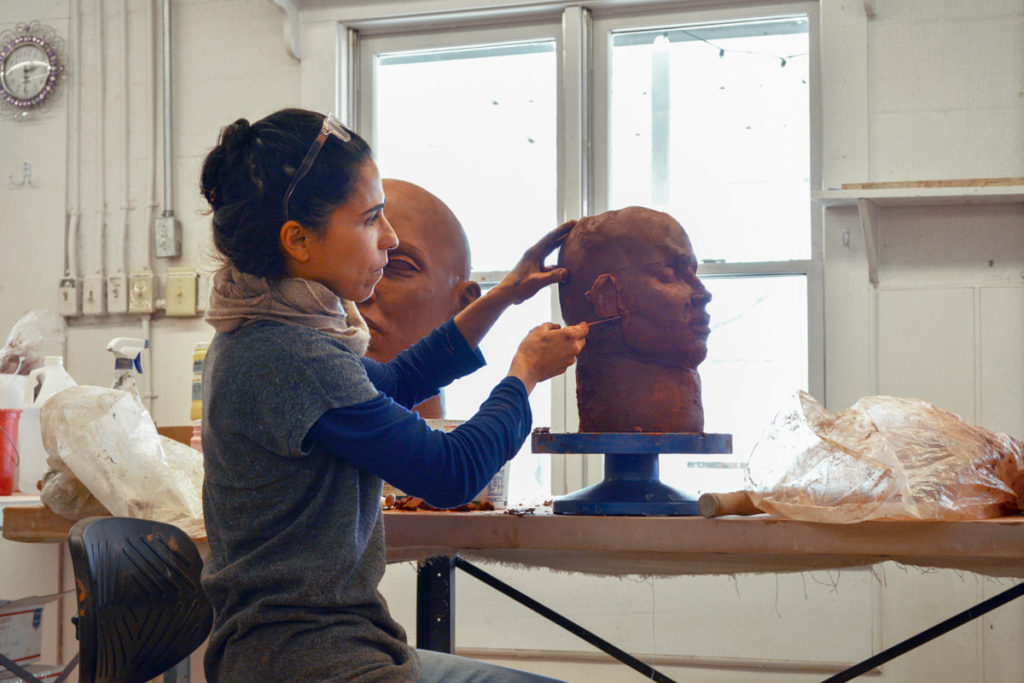 Cristina Cordova refines the features on the side of the clay head she is sculpting