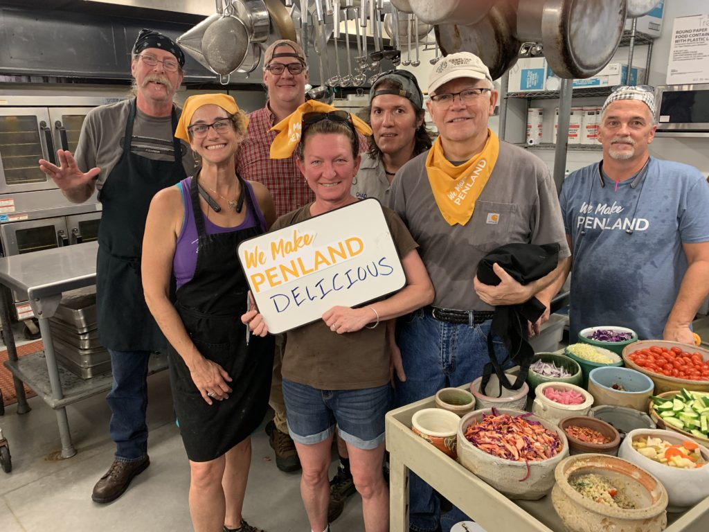 "Penland's kitchen crew standing with a sign that reads ""We Make Penland Delicious!"""