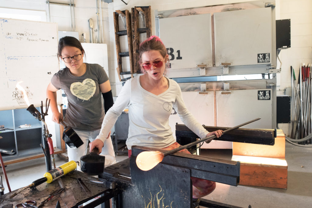 Two women blowing glass in the Penland School of Craft hot shop