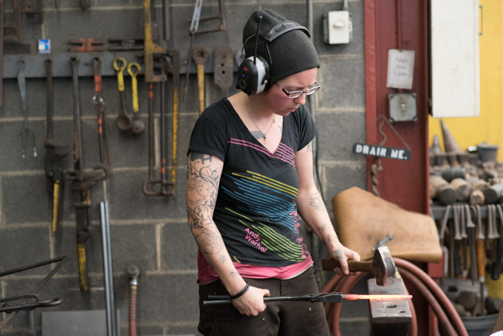 A woman working at the anvil in the Penland School of Craft iron studio