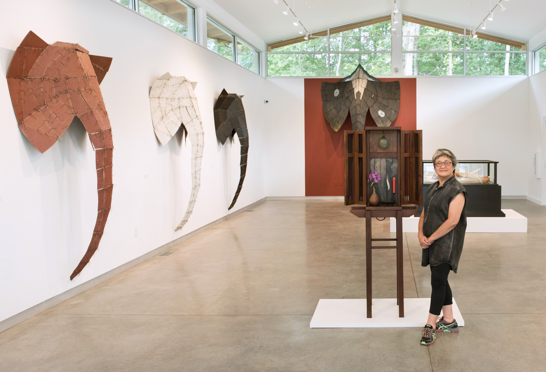 Wendy Maruyama standing next to a wooden shrine with elephant masks behind