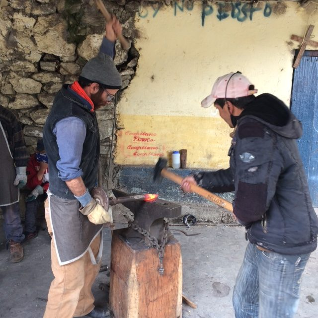 Daniel and a student working at the anvil