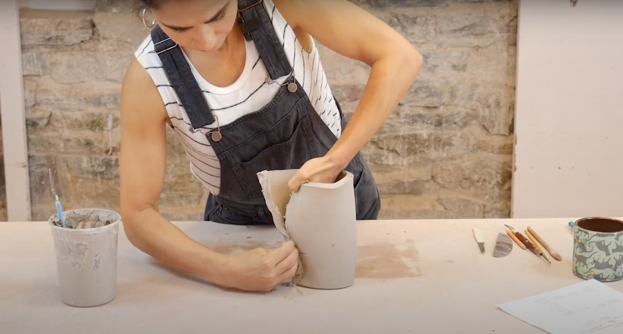 Cristina forming a clay slab into the beginnings of a head
