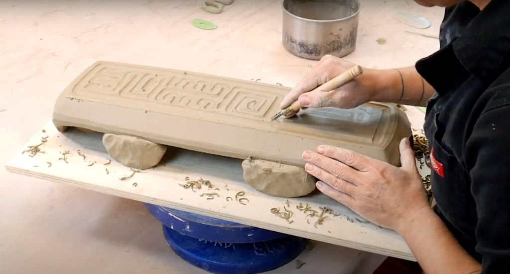 Courtney Martin uses a loop tool to carve a geometric pattern into the underside of her clay tray