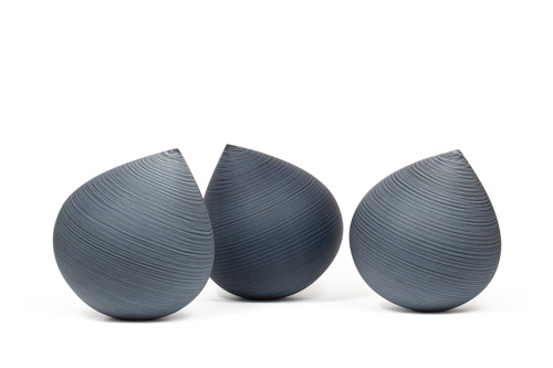 Three grey glass droplets with subtle horizontal striping