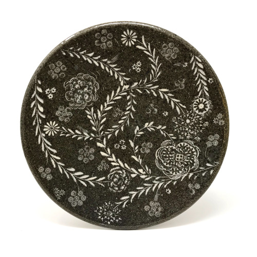 Dark plate with delicate white flower and leaf pattern