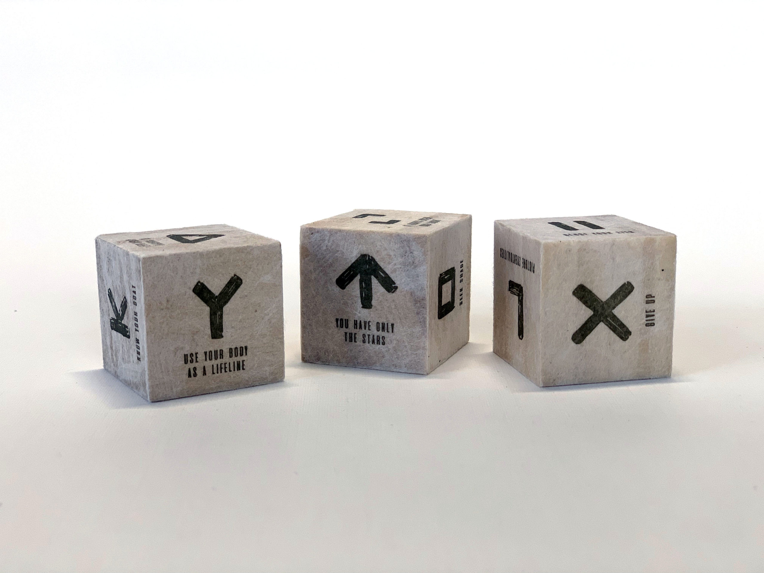 three cubes printed with symbols and directions on each side