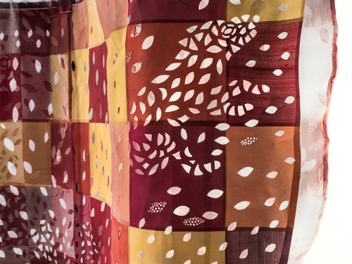 textile hanging with squares of red, yellow, and orange printed with white