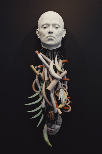 Sculpture of a human head with various objects suspended beneath it