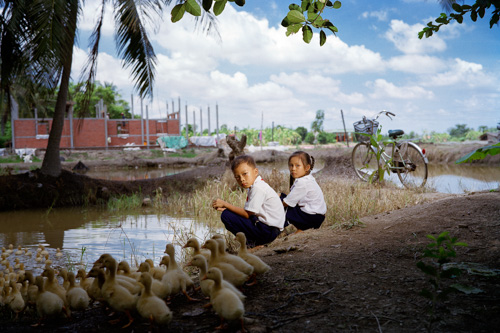 photograph of two children kneeling next to water with ducks