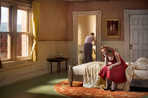 photograph of a woman in a red dress sitting on a bed with a man visible in the bathroom behind her