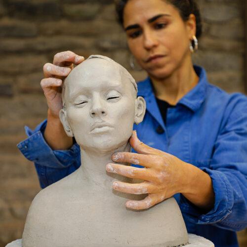 Cristina Córdova working on a ceramic head in the Penland clay studio