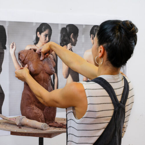 Cristina Córdova working on a ceramic torso in the Penland clay studio