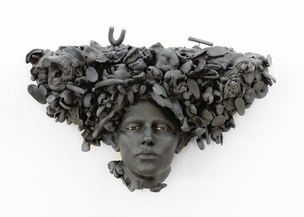 black ceramic sculpture of a head with ornate hair